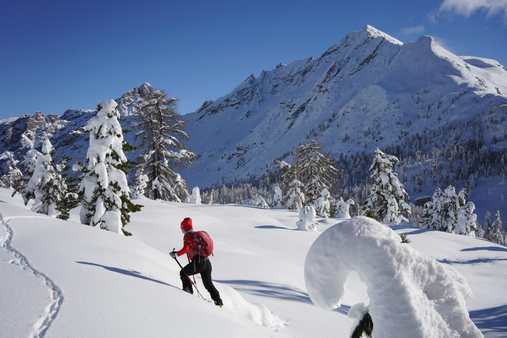 Girl on skis uphill on a deep snow slope in the Dolomites