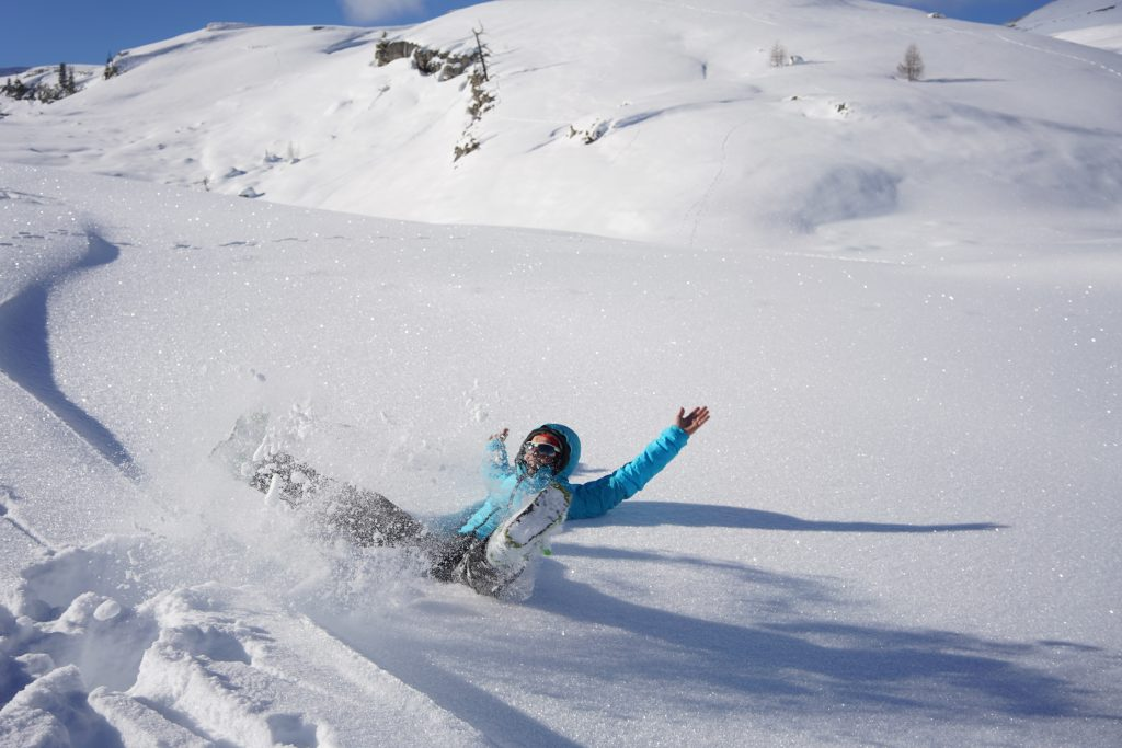 Girl with blue jacket sitting in the snow with her arms and legs in the air in the dolomites
