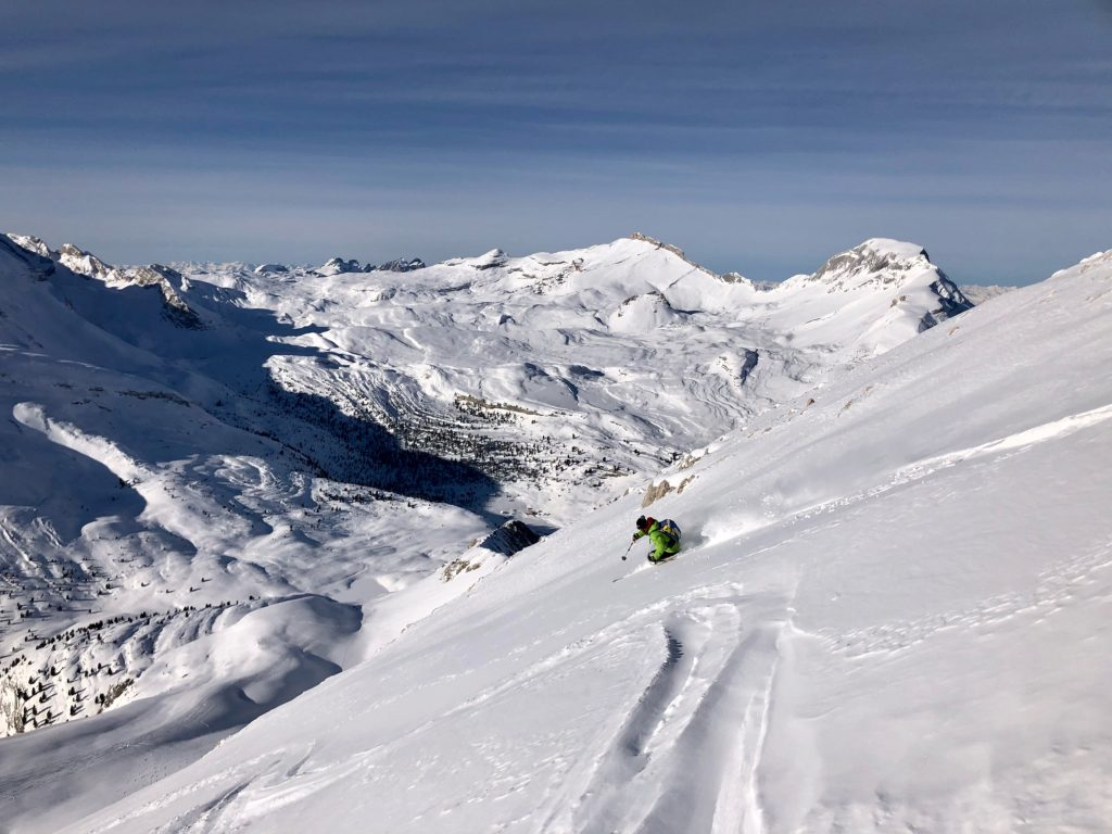 Girl on skis downhill on a deep snow slope in the Dolomites